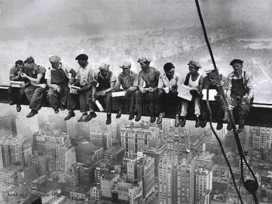 American construction workers having lunch midair on a crossbeam over New York City. Photographer: Charles C. Ebbets.