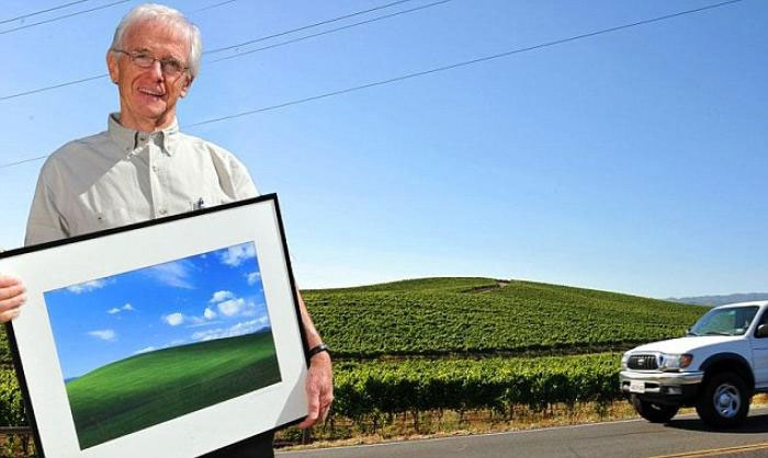 Charles O'Rear holding the iconic Bliss photograph at the real location where the photograph was taken.