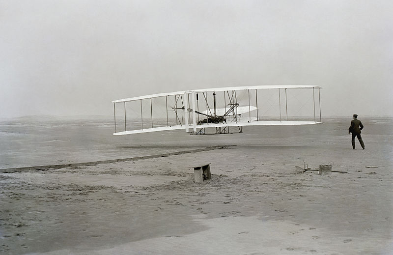 The First Flight. Orville is piloting the plane. Wilbure is standing near the wingtip. Photograph by John T. Daniels.