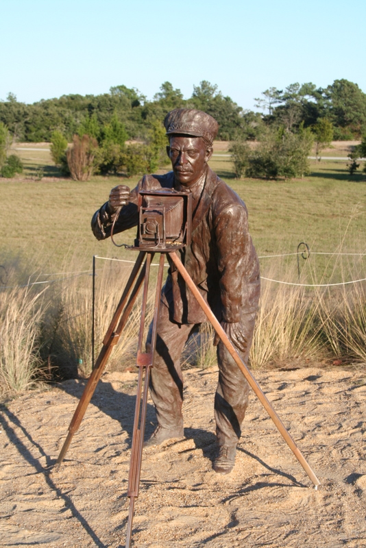 Broze statue of John T. Daniels taking the photograph First Flight.