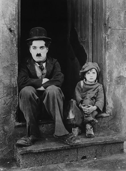 Charlie Chaplin and Jackie Coogan in movie The Kid (1921). This photograph was used for the publicity of the film. Photographer unknown.
