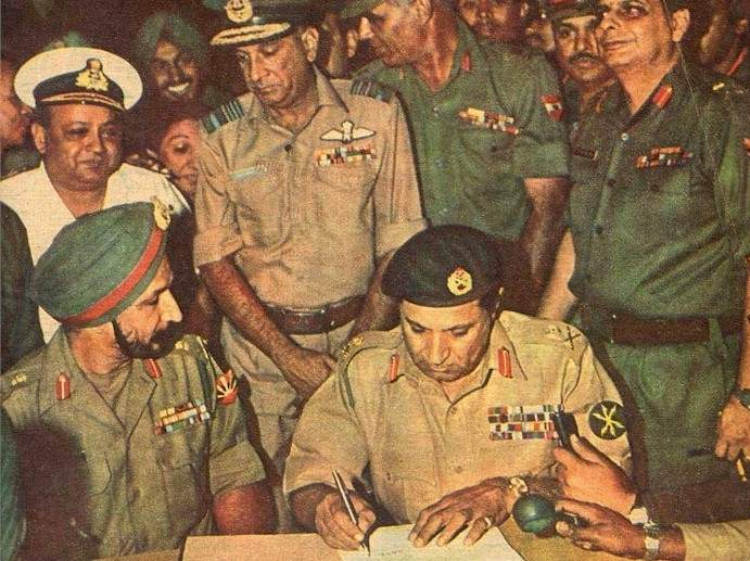 Lieutenant General A. A. K. Niazi (right) signing the Instrument of Surrender while surrendering to Lieutenant General Jagjit Singh Arora of the Indian Army (left).