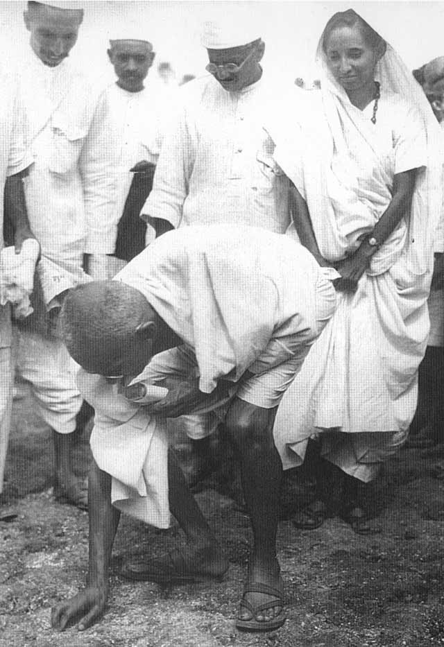 Mahatma Gandhi gathering salt to break salt law at the end of Dandi March on 6 April 1930.