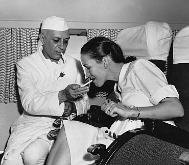 Jawaharlal Nehru smoking and lighting cigarette. Photograph by Homai Vyarawalla.