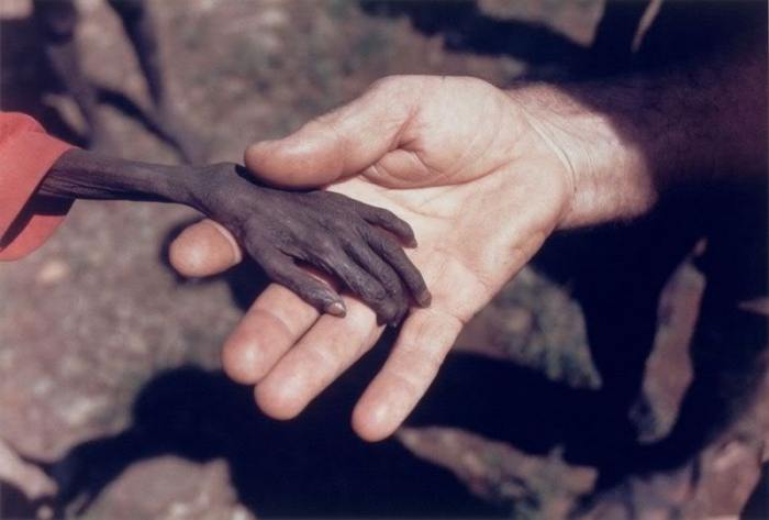 A missionary holding hand of an emaciated Ugandan boy during the Uganda Karamoja famine. Photograph by Mike Wells.