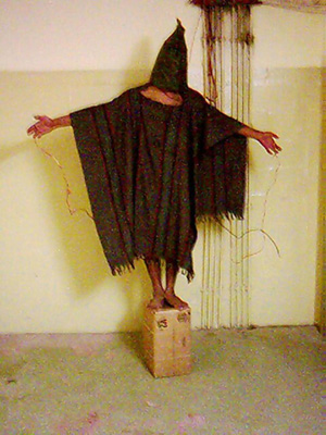 A detainee in Abu Gharib prison standing on a box with wires attached to his hands.