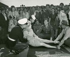 Betty Grable being held on a wet contrete slab for her leg-print at Grauman's Chinese Theater.